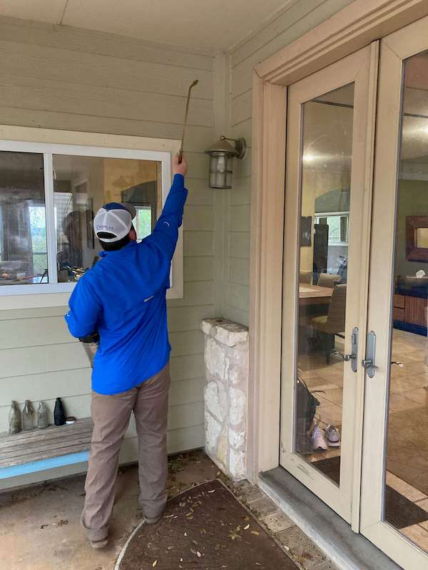 exterminator or pest control technician spraying outside home